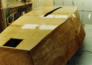 Bottom and side skins have been completed and the whole hull glassed over. The aperture for the outboard motor and the centre board slot can be clearly seen. The centerboard is constructed from jarrah and oregan and has a lead shoe.